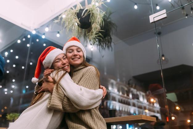 Portrait de jeunes amis mignons heureux s'embrassant au caffe