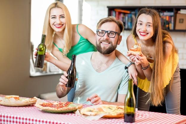 Portrait des jeunes amis vêtus avec désinvolture de t-shirts colorés en train de déjeuner avec pizza et bière à la maison