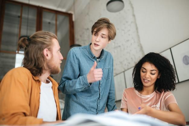 Portrait de jeunes discutant de quelque chose au bureau. deux garçons aux cheveux blonds et fille aux cheveux bouclés sombres étudient ensemble en classe