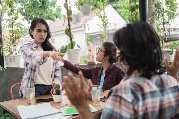 Portrait de jeunes étudiants asiatiques réunis dans un café. ennuyé avec son ami masculin et l'a pointé