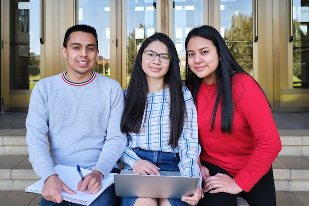 Portrait de jeunes étudiants hispaniques à l'entrée d'un campus universitaire