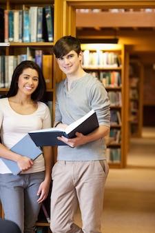 Portrait de jeunes étudiants avec un livre dans la bibliothèque
