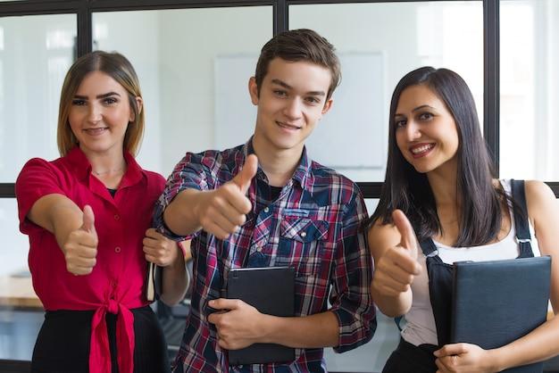 Portrait de jeunes étudiants réussis montrant les pouces vers le haut