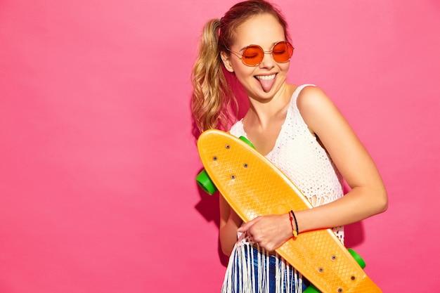 Portrait de jeunes femmes blondes souriantes élégantes avec planche à roulettes penny. femmes en robe blanche d'été posant près du mur rose