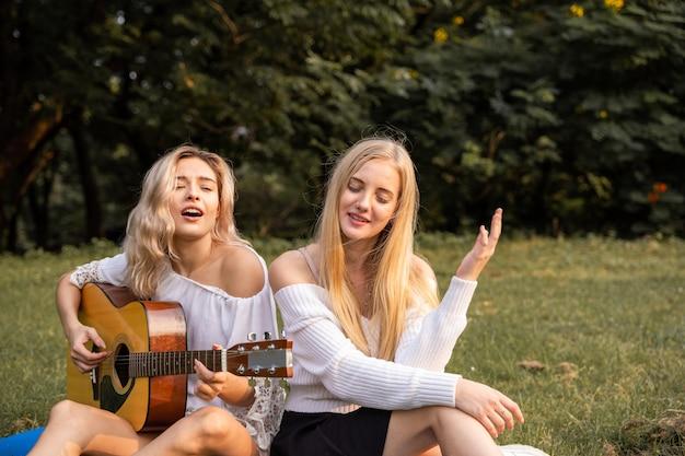 Portrait de jeunes femmes caucasiennes assises dans le parc en plein air et jouant de la guitare chantent une chanson avec bonheur