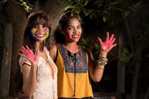 Portrait de jeunes filles heureux s'amusant avec de la poudre colorée au festival de couleurs holi