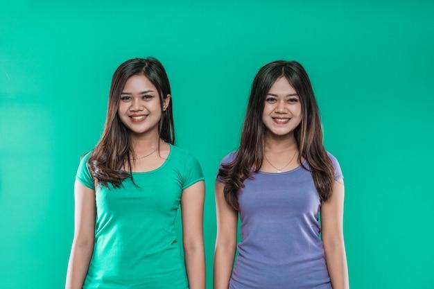 Portrait de jeunes filles twins nice cute charmant joyeux avec des cheveux raides isolé sur fond vert