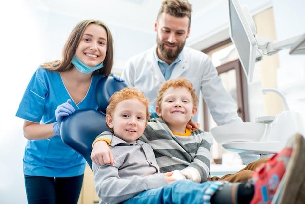 Portrait de jeunes garçons heureux assis sur la chaise avec un dentiste et une assistante au cabinet dentaire