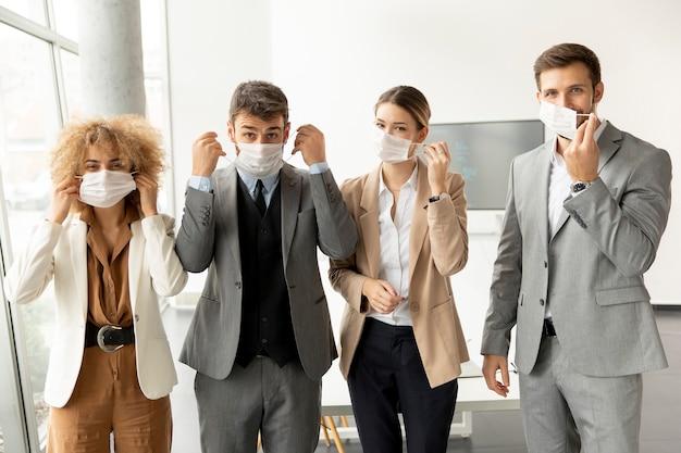 Portrait de jeunes gens d'affaires qui décollent leurs masques de protection au bureau
