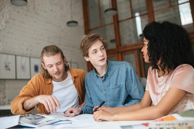 Portrait de jeunes gens cool travaillant au bureau. deux garçons aux cheveux blonds et fille aux cheveux bouclés foncés assis et étudiant ensemble en classe