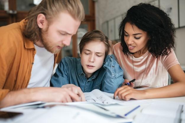 Portrait de jeunes gens discutant pensivement de quelque chose au bureau. deux garçons aux cheveux blonds et fille aux cheveux bouclés foncés travaillant sur un nouveau projet en classe