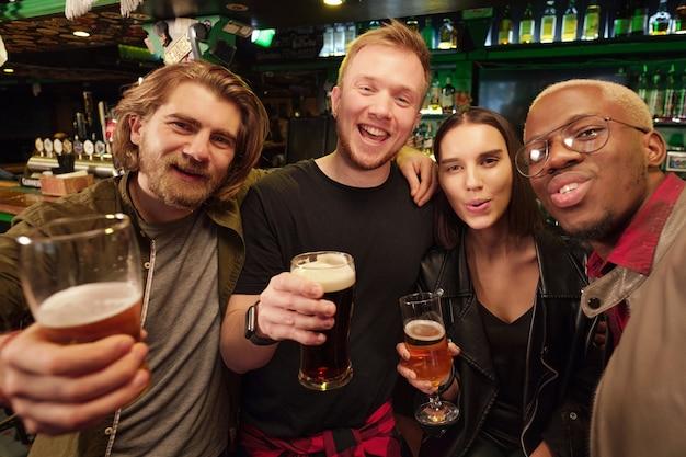 Portrait de jeunes heureux buvant de la bière et souriant à la caméra en se tenant debout dans le pub