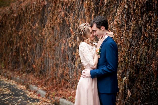 Portrait de jeunes mariés heureux dans la nature en automne.