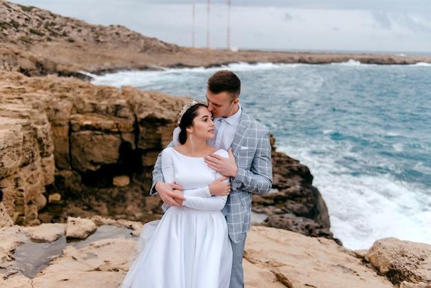Portrait de jeunes mariés heureux sur le rivage rocheux de la mer
