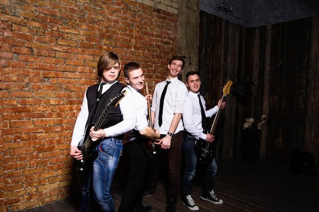 Portrait de jeunes musiciens branchés sur un mur de briques