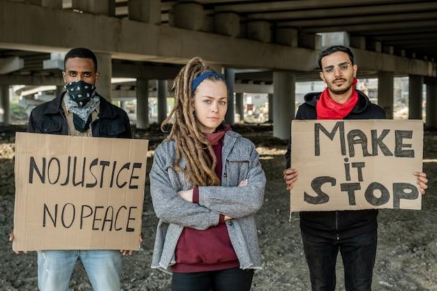 Portrait de jeunes personnes interraciales sérieuses debout avec des panneaux sous le pont tout en participant à une manifestation