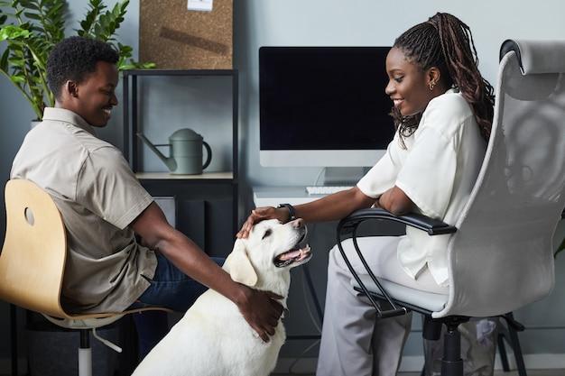 Portrait de jeunes souriants caressant un chien tout en travaillant dans un espace de copie de bureau adapté aux animaux de compagnie