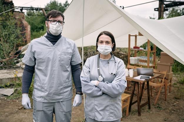 Portrait de jeunes travailleurs médicaux portant des masques et des gommages debout contre une tente avec des médicaments dans des réfugiés...