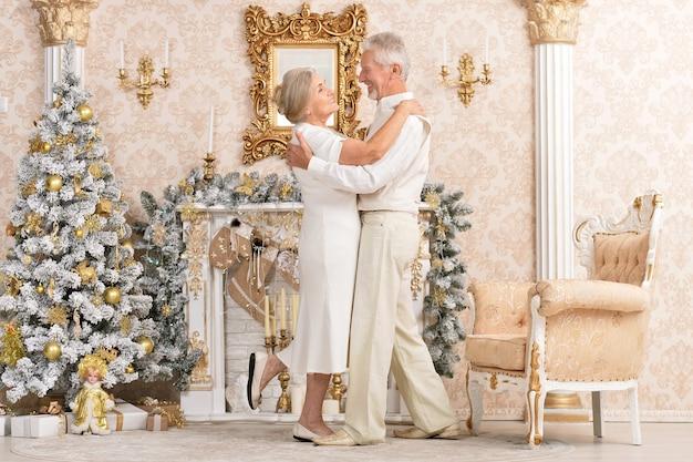 Portrait d'un joli couple de personnes âgées heureux dansant près de l'arbre de noël