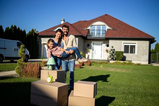Portrait d'un joli couple tenant leur fille devant leur nouvelle maison.