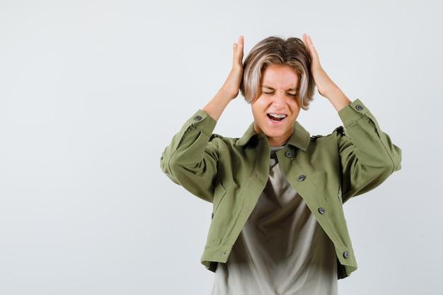 Portrait d'un joli garçon adolescent gardant les mains sur la tête en veste verte et regardant la vue de face irritée