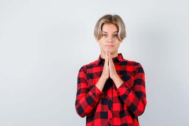 Portrait d'un joli garçon adolescent avec les mains en geste de prière en chemise à carreaux et à la vue de face pleine d'espoir