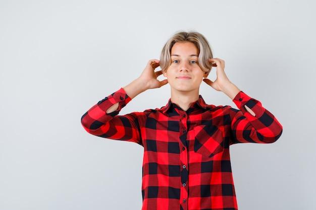 Portrait d'un joli garçon adolescent avec les mains près des oreilles en chemise à carreaux et à la vue de face joyeuse