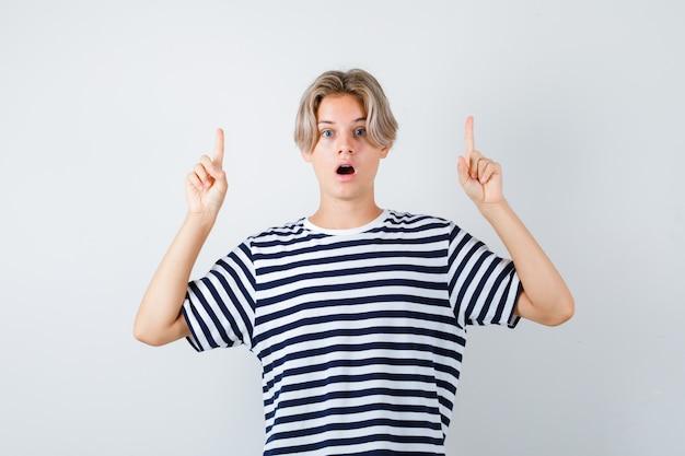Portrait d'un joli garçon adolescent pointant vers le haut en t-shirt rayé et regardant la vue de face choquée