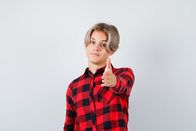 Portrait d'un joli garçon adolescent qui s'étend la main à l'avant en chemise à carreaux et à la vue de face confiante