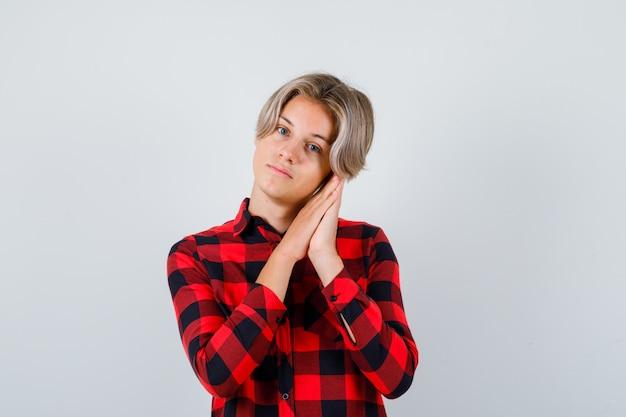 Portrait de joli garçon adolescent s'appuyant sur les paumes comme oreiller en chemise à carreaux et à la vue de face sensible