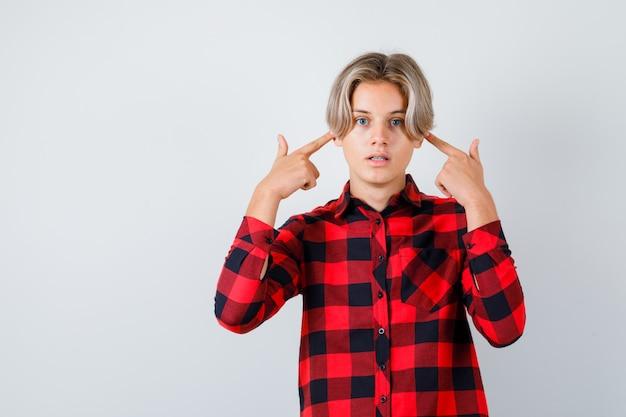 Portrait d'un joli garçon adolescent se branchant les oreilles avec les doigts en chemise à carreaux et à la vue de face effrayée