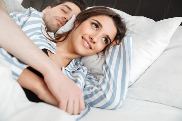 Portrait d'un joli jeune couple couché ensemble