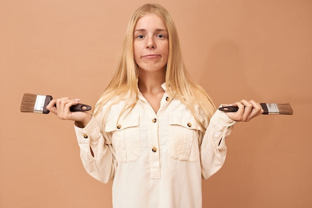 Portrait de jolie adolescente avec des accolades et des cheveux longs à l'aide d'outils spéciaux tout en peignant les murs intérieurs pour les protéger des dommages causés par l'eau ou la corrosion