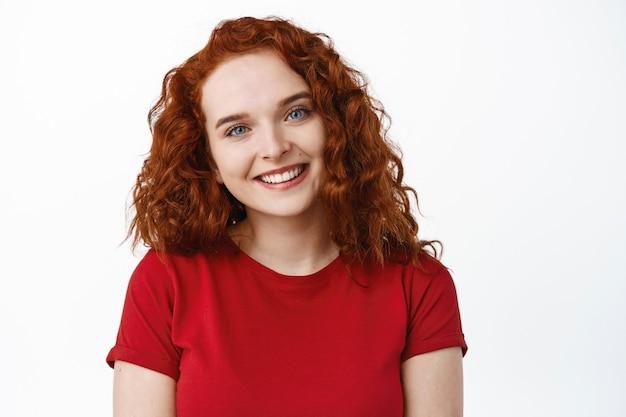 Portrait d'une jolie adolescente aux cheveux roux bouclés et à la peau naturelle pâle sans maquillage, tête inclinée et sourire amical, debout sur un mur blanc