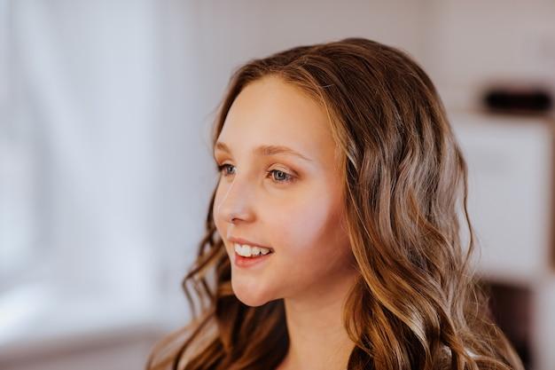 Portrait de jolie adolescente avec coiffure frisée et maquillage léger. copiez l'espace.
