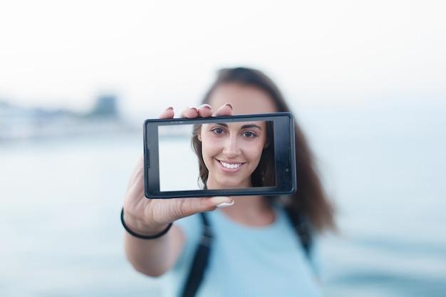 Portrait d'une jolie adolescente debout sur une plage de sable d'été en vacances, tenant un smartphone prenant des photos d'elle-même en vacances contre le ciel bleu. les gens voyagent avec la technologie.