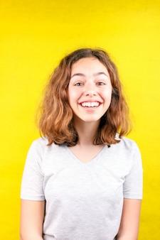 Portrait de jolie adolescente gaie bouclée rire