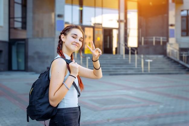 Portrait de jolie adolescente joyeuse en t-shirt blanc avec sac à dos noir sur son épaule. élève du secondaire élégant fait des gestes avec ses mains sur le fond du bâtiment du collège.