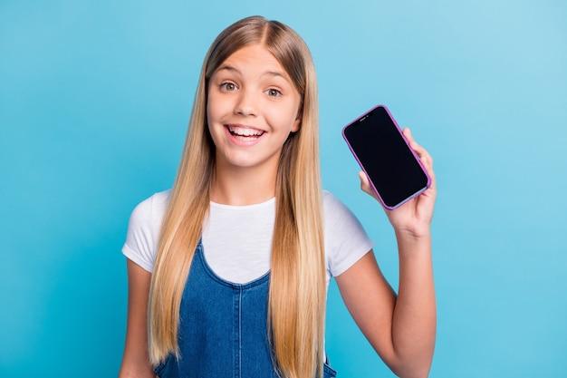 Portrait d'une jolie adolescente optimiste montrant le téléphone de la publicité portant un look décontracté isolé sur fond de couleur bleu pastel