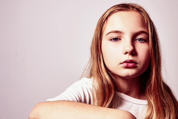Portrait d'une jolie adolescente pensive aux cheveux longs.