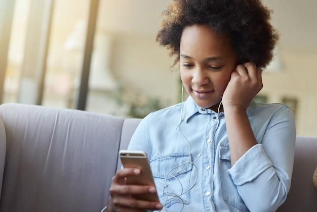 Portrait d'une jolie adolescente de race mixte mettant des écouteurs assis sur le canapé et utilisant un mobile