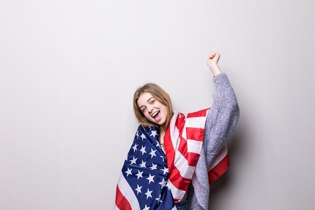 Portrait de jolie adolescente tenant le drapeau des usa isolé sur fond gris. fête du 4 juillet.