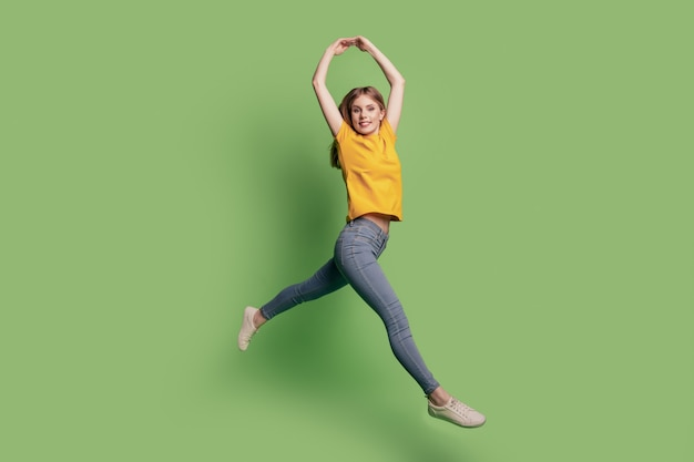 Portrait de jolie ballerine charmante lady jump dance wear t-shirt jaune jeans chaussures sur fond vert