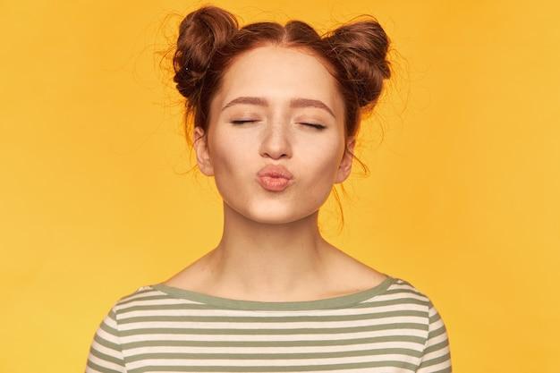 Portrait de jolie, belle fille aux cheveux roux avec deux petits pains et une peau saine. doux baiser les yeux fermés. porter un pull rayé et se tenir isolé, gros plan sur mur jaune