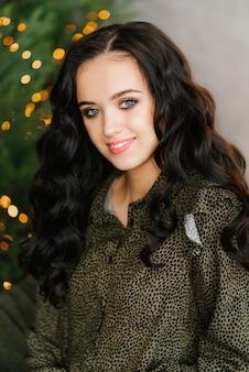 Portrait d'une jolie brune avec un maquillage professionnel sur fond de lumières