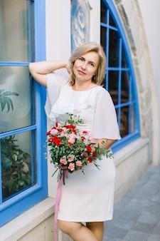Portrait d'une jolie charmante dame blonde agréable de 40 ans en robe blanche élégante, tenant un bouquet de fleurs et posant près du bâtiment vintage de la ville avec une grande fenêtre bleue