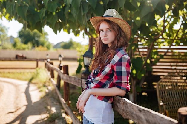 Portrait de jolie cowgirl rousse souriante au chapeau s'appuyant sur la clôture du ranch