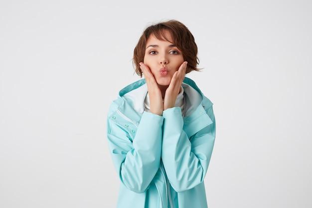 Portrait de jolie dame bouclée aux cheveux courts en golf blanc et manteau de pluie bleu clair, se dresse sur fond blanc et envoie un baiser à la caméra.