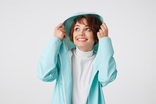 Portrait de jolie dame bouclée aux cheveux courts souriante en golf blanc et manteau de pluie bleu clair, se cachant sous le capot et levant les yeux, se dresse sur fond blanc.