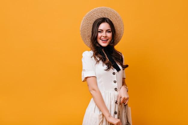 Portrait de jolie dame bouclée en chapeau de paille et robe blanche sur fond orange.